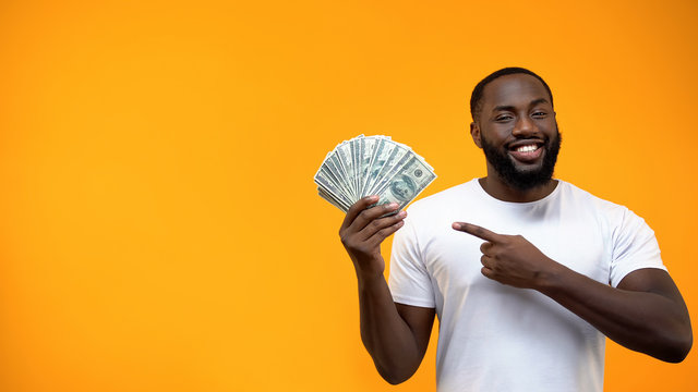 African-American man pointing finger into bunch of dollars, capital investment