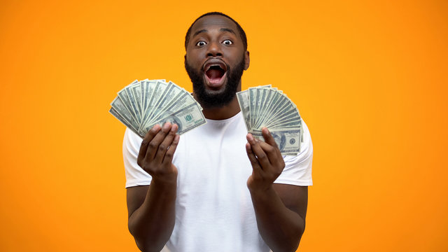 Astonished Afro-American man holding bunches of dollars, lucky lottery winner