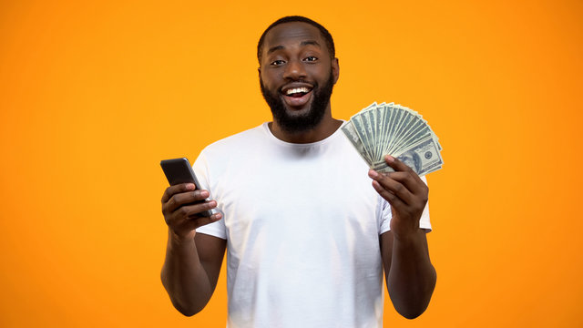 Excited Afro-American man holding smartphone and dollars, online money transfer