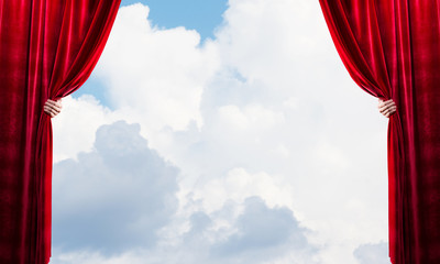 Cloudy landscape behind red curtain and hand holding it