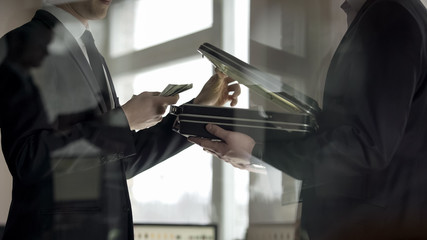Lawyer opening case and looking at money, concept of illegal job offer, bribe