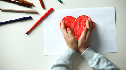 Kid putting hands on red heart picture, childhood and love, charity concept