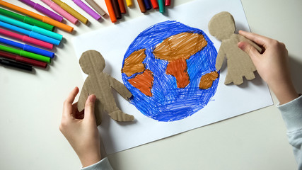 Kid putting paper family on Earth painting, environmental saving concept Wall mural