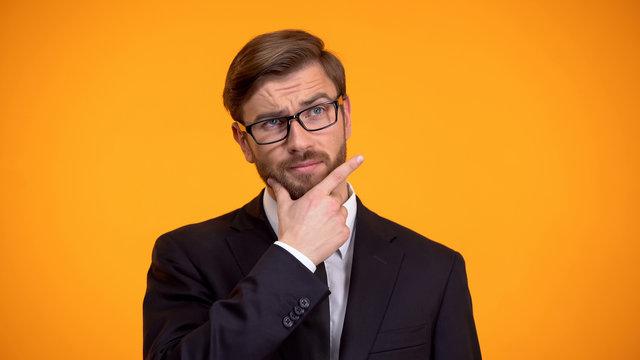 Businessman scratching chin thinking over start-up strategy, orange background