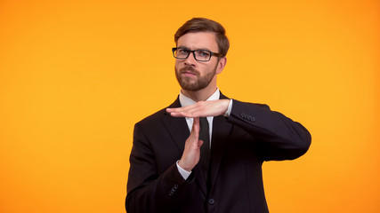 Business person showing time-out gesture, isolated on orange background deadline