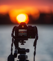 digital camera on a tripod taking pictures of sunset over the lake