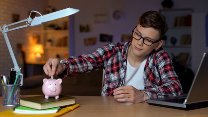 Teenager putting money to piggyback, freelancer, work for students, first salary Wall mural