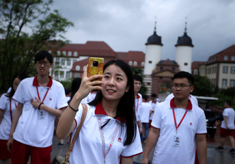 A newly recruited fresh graduate takes a photo at Huawei Songshan Lake New Campus in Dongguan