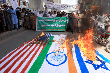 People chant slogans as they set on fire the representation of India, Israel and U.S. flags in a rally, marking al-Quds Day, (Jerusalem Day), during the Muslim holy month of Ramadan in Peshawar