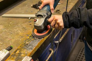 95ae6953 Eine Frau bearbeitet ein Stück Eisen mit dem Winkelschleifer