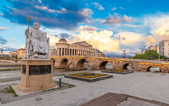 SKOPJE, NORTH MACEDONIA - 25.04.2019: Byzantine Emperor Justinian Statue and Stone Bridge, behind the Archeology Museum at sunset in Skopje