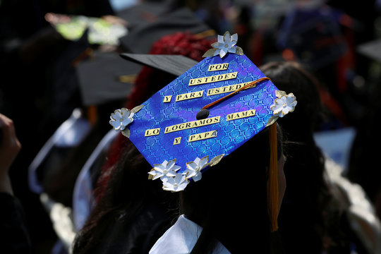 """An adorned graduation cap written in Spanish saying, """"For you by you. We did it mom and dad,"""" at The City College of New York commencement ceremony in Manhattan"""