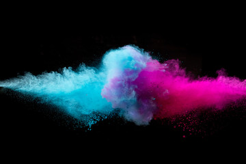 Colored powder collision on black background. Freeze motion.