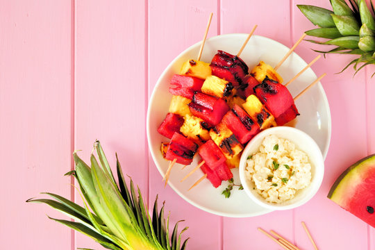Grilled watermelon and pineapple fruit skewers with feta. Top view on a pink wood background. Summer food concept.