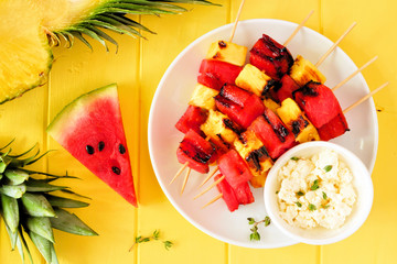 Grilled watermelon and pineapple fruit skewers with feta. Above view on a bright yellow wood background. Summer food concept.