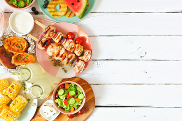 Summer BBQ or picnic food side border. Selection of grilled meat, fruits, salad and potatoes. Above...