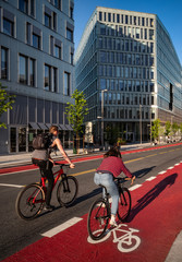 Couple cycling along a bicycle-marked red lane in a business area in Oslo, Norway.