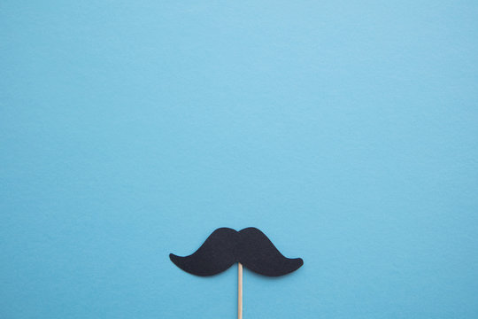 Black paper mustache on a blue background. Father's day or mens health concept