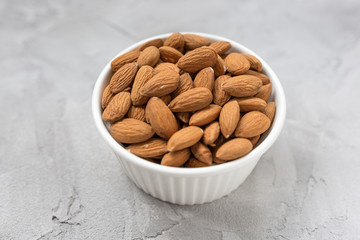 Raw almonds in a porcelain bowl on a gray background