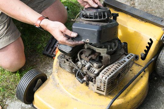 Man repairing an old lawn mower