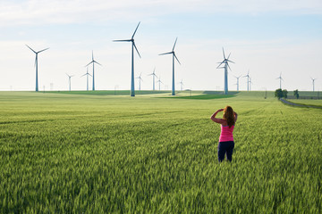 Young woman looking towards wind turbines at sunrise, in a field of green wheat. Concept for sustainable energy solutions in the future. Wall mural