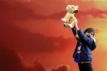 A girl poses for a photo with a stuffed Simba toy in her hands during Comic Con Colombia in Bogota