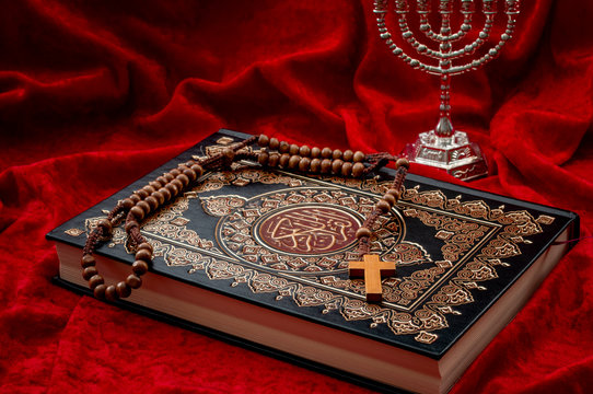 Religious coexistence, monotheism and abrahamic religions coexist in peace concept theme with a quran representing islam, a cross and rosary symbolizing christianity and menorah a symbol of judaism