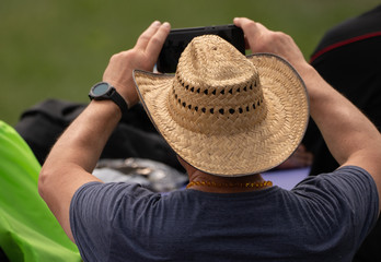 unknown man is taking a picture of the event with his cell phone camera
