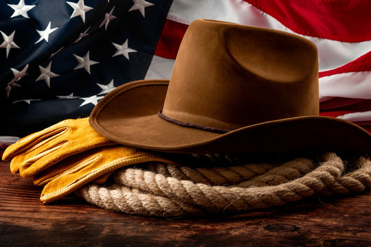 American culture, independence day in the United States of America and 4th of july concept theme with a cowboy hat, USA flag, rope lasso and farm gloves on a wooden background in a old saloon