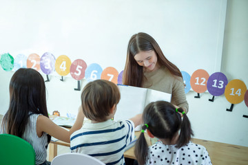 Asian woman teaching children reading a book in a class of preschool. international School