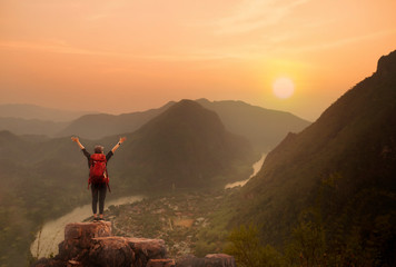 Backpacker woman standing on top of mountain and open arm with sunset ore sunrise background Wall mural
