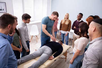 Man Giving Teaching Massage To Group Of People