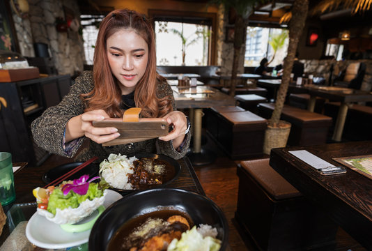 woman using smartphone taking a photo of food in restaurant