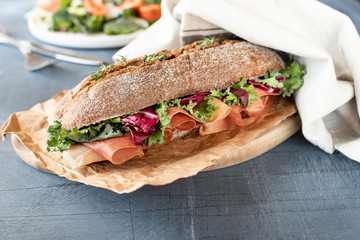 sandwich with baguette, ham, lettuce, kale on gray background, salad from kale and lettuce leaves and tomatoes on a white plate. healthy diet lunch, takeaway sandwich