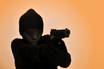 Female robber with black gloves and tights over her head holding a gun and aiming.  Selective focus.