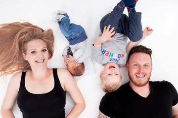 Glückliche Familie liegt am Boden und hat Spaß