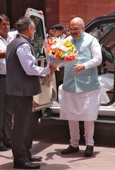 India's newly appointed Home Minister Amit Shah receives a flower bouquet upon his arrival at the home ministry in New Delhi