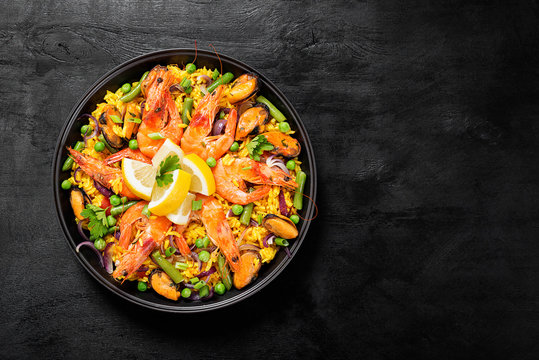 Traditional spanish seafood paella in the fry pan on a black wooden  table, top view.