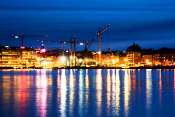 Fototapete - View of Gamla Stan in Stockholm, Sweden with construction cranes during the night