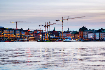 Fototapete - View of Gamla Stan in Stockholm, Sweden with construction cranes during the evening