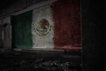 painted flag of mexico on the dirty old wall in an abandoned ruined house.