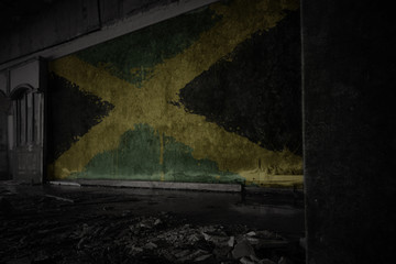 painted flag of jamaica on the dirty old wall in an abandoned ruined house.