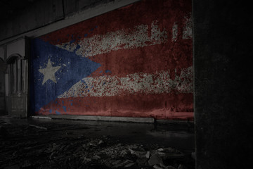 painted flag of puerto rico on the dirty old wall in an abandoned ruined house.