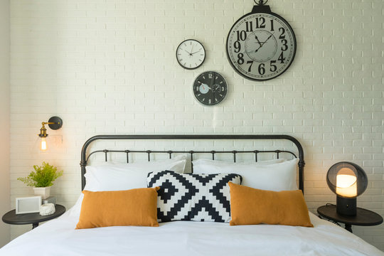 Comfortable bed with yellow and grey bedding, industrial style clock on wall.