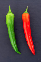 parallel vertical green red chili pepper on a black background long pods close-up