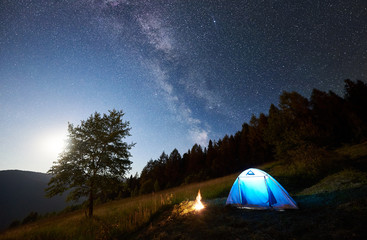 Tourist camping near forest at summer night. Illuminated tent and campfire under magical night sky full of stars and Milky way. On background big tree, beautiful starry sky, mountains and full moon