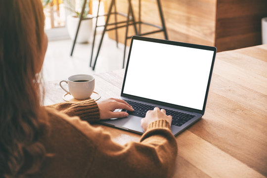 Mockup image of a woman using and typing on laptop computer keyboard with blank white desktop screen with coffee cup on wooden table