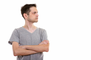 Profile view of angry young man with arms crossed