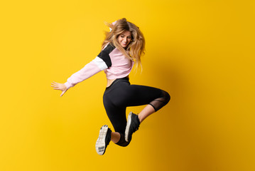 Foto op Canvas Dance School Urban Ballerina dancing over isolated yellow background and jumping