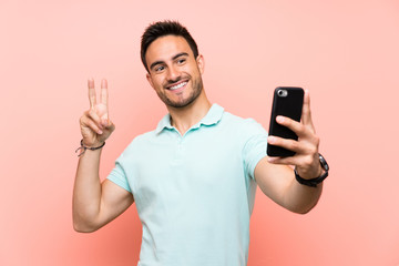 Handsome young man over isolated background making a selfie